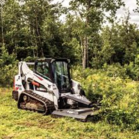 Photo of Bobcat Skid Steer Loader With Front-Mounted Rotary Cutter Bush Hogging Overgrown Pasture On Steep Hill