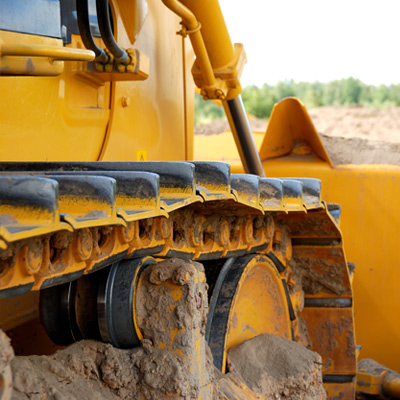 Detail Photo of Tracks on Buildozer That Is Moving Dirt Around During a Grading and Excavation Operation