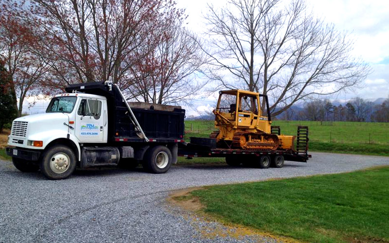 Photo of Bulldozer, Equipment Trailer, and Dump Truck Heavy Equipment of Practical Property Management