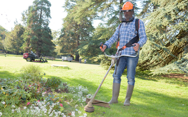 Photo of Landscaping Worker Trimming Garden Bed With String Trimmer