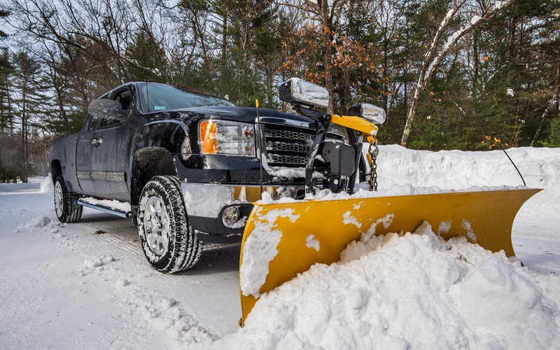 Photo of Heavy Duty Pickup Truck With Snowplow and Salt Spreader Plowing Snow for Commercial Customer