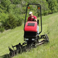 Photo of Operator Driving Steep Slope Mowing Machine Cutting Grass on Very Steep Hill